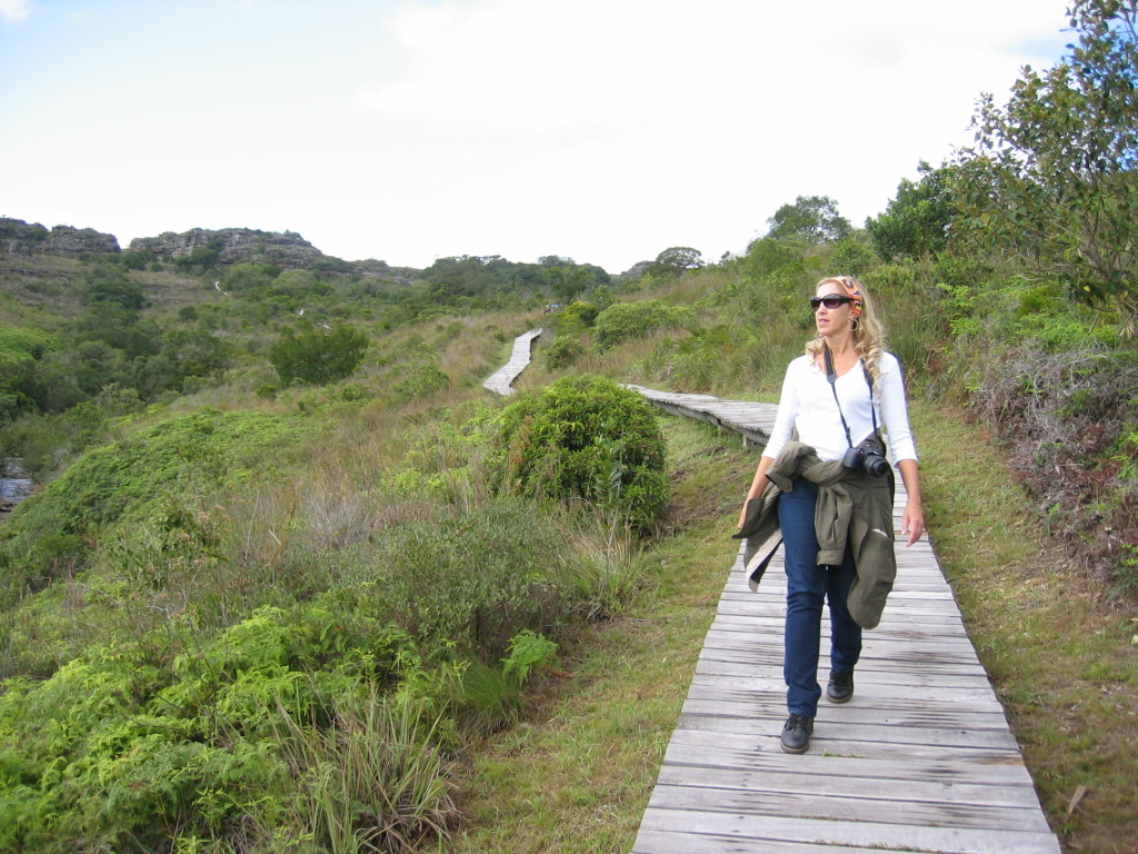 Theresa walking on a wooden pathway at the State Park of Guartelá.